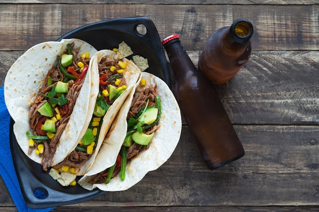 Mexican fajitas with beer in a black ceramic tray on old wooden boards. copy space. mexican food concept.