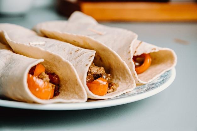 Мексиканские фахитас с веганскими приправами на тарелке на кухне с перцем