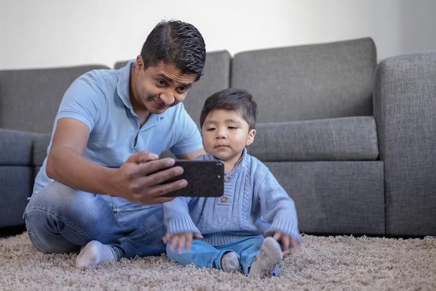 自宅のカーペットの上で電話を見ているメキシコの父と息子