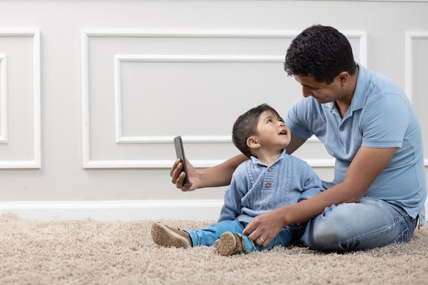 멕시코 아버지와 아들 집에서 카펫에 전화를보고