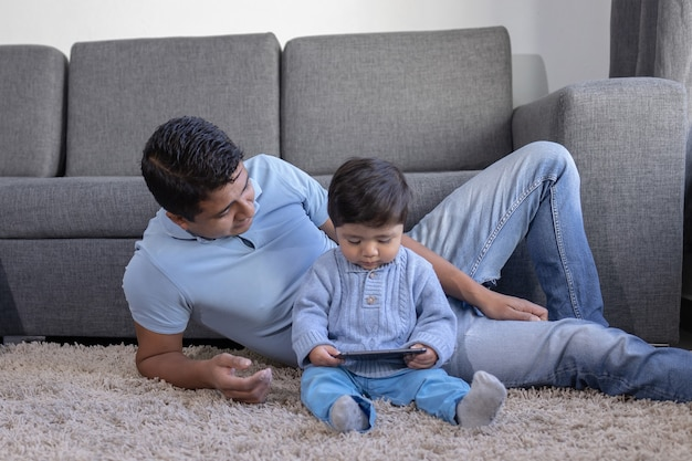 Mexican father and son looking at phone on carpet at home