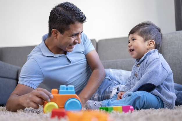 Mexican father and son playing on carpet at home,