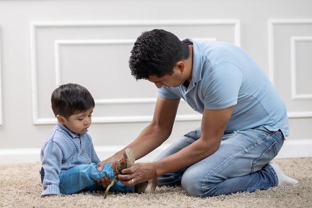 メキシコ人の父親が息子に靴を締める