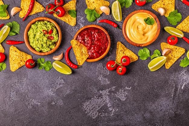 멕시코 음식 배경:과카몰리, 살사, 검은 배경에 재료를 넣은 치즈 소스, 위쪽 전망.