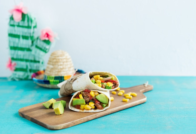 Mexican food. burritos on kitchen table on blue background. mexican cuisine concept. copy space.
