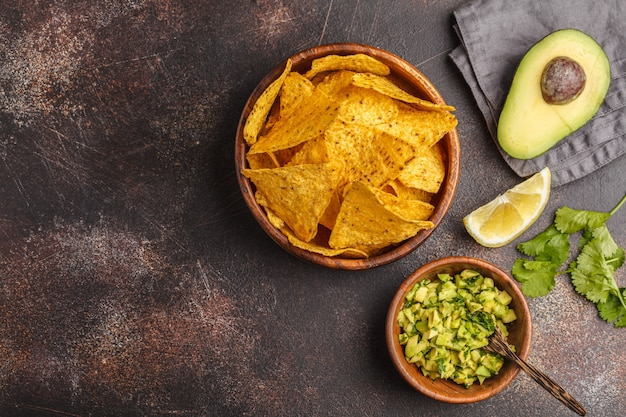 Mexican food concept. nachos - yellow corn totopos chips with guacamole, frame of food, top view, copy space.