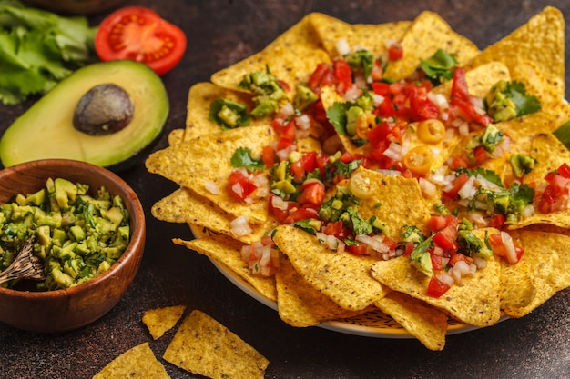 Mexican food concept. nachos - yellow corn totopos chips with various sauces in wooden bowls: guacamole, cheese sauce, pico del gallo