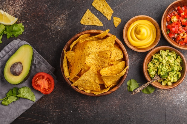 Mexican food concept. nachos - yellow corn totopos chips with various sauces in wooden bowls: guacamole, cheese sauce and tomato sauce, copy space, top view