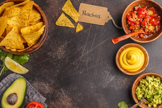 Mexican food concept. nachos - yellow corn totopos chips with various sauces in wooden bowls: guacamole, cheese sauce and tomato sauce, frame of food, top view, copy space.
