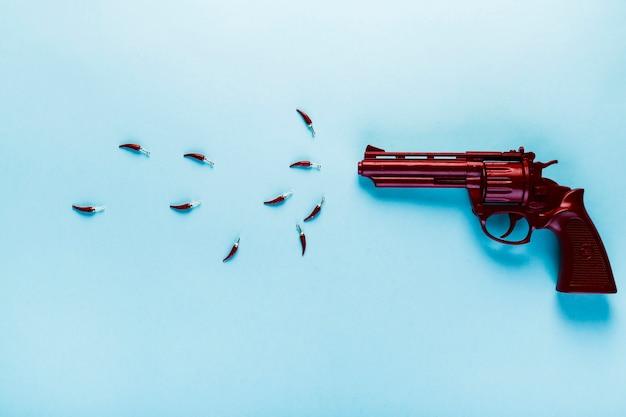 銃と小さなchilisとメキシコの食べ物のコンセプト