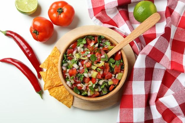 白い背景の上のピコデガロとメキシコ料理のコンセプト
