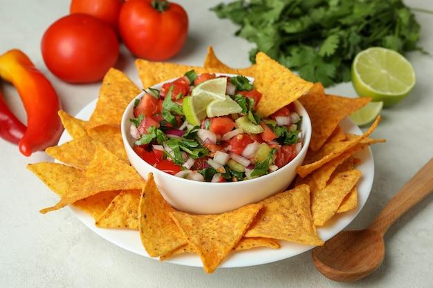 白い織り目加工のテーブルにピコデガロとメキシコ料理のコンセプト