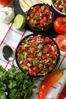 白い木製のテーブルにピコデガロとメキシコ料理のコンセプト