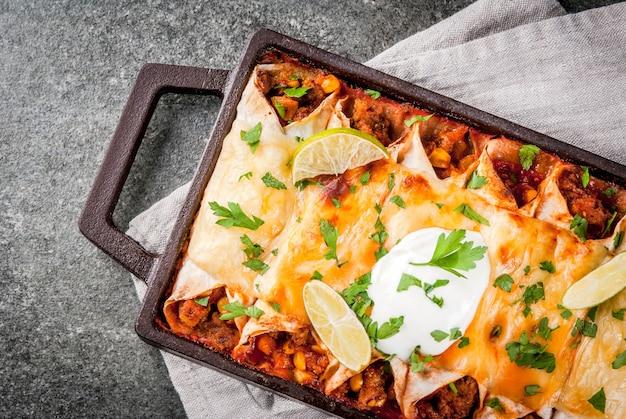 Мексиканская еда. кухня южной америки. традиционное блюдо из острой говяжьей энчиладас с кукурузой, фасолью, помидорами. на противне, на черном каменном фоне. вид сверху копией пространства