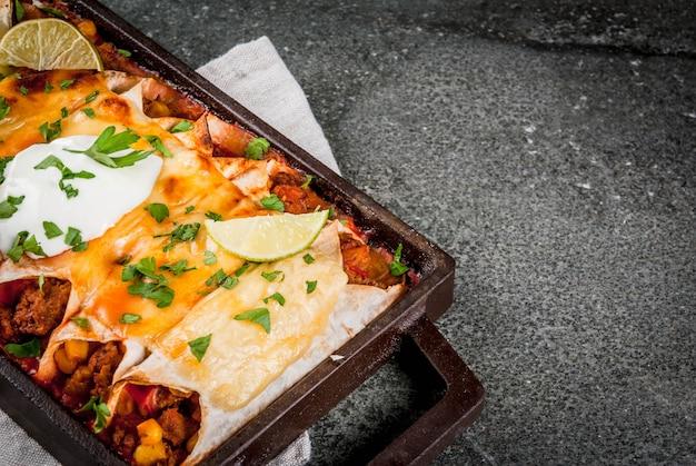 Мексиканская еда. кухня южной америки. традиционное блюдо из острой говяжьей энчиладас с кукурузой, фасолью, помидорами. на противне, на черном камне.