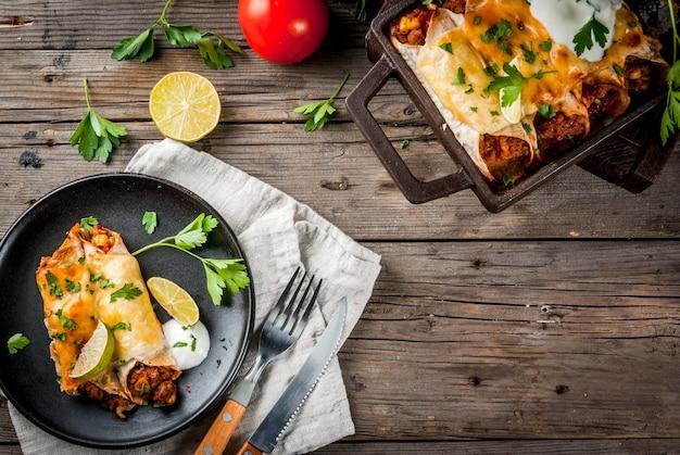Мексиканская еда. кухня южной америки. традиционное блюдо из острой говяжьей энчиладас с кукурузой, фасолью, помидорами. на противень, на старый деревенский деревянный фон. скопировать вид сверху