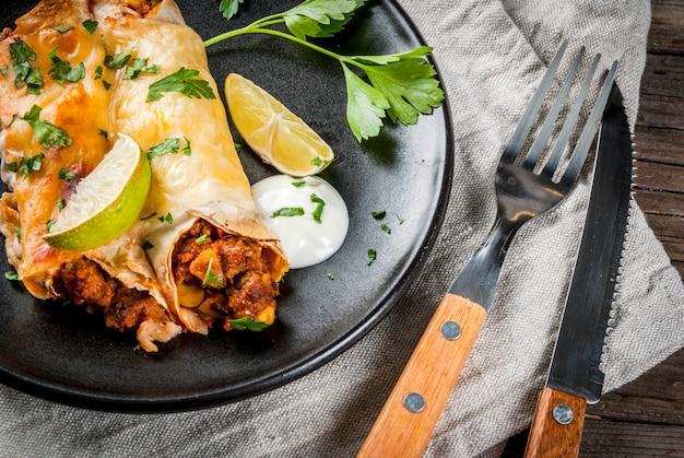 Мексиканская еда. кухня южной америки. традиционное блюдо из острой говяжьей энчиладас с кукурузой, фасолью, помидорами. на противень, на старый деревенский деревянный фон. копировать пространство