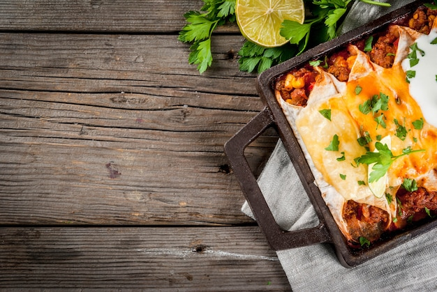 Мексиканская еда. кухня южной америки. традиционное блюдо из острой говяжьей энчиладас с кукурузой, фасолью, помидорами. на противень, на старый деревенский деревянный фон. вид сверху копией пространства