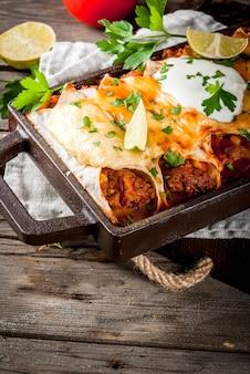 Мексиканская кухня кухня южной америки традиционное блюдо из острой говяжьей энчилада с помидорами из кукурузной фасоли на противне для выпечки на старом деревенском деревянном фоне