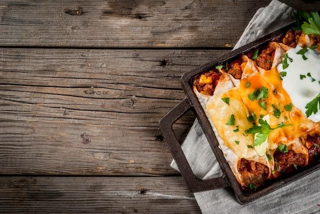 Мексиканская еда. кухня южной америки. традиционное блюдо из острой говяжьей энчиладас с кукурузой, фасолью, помидорами