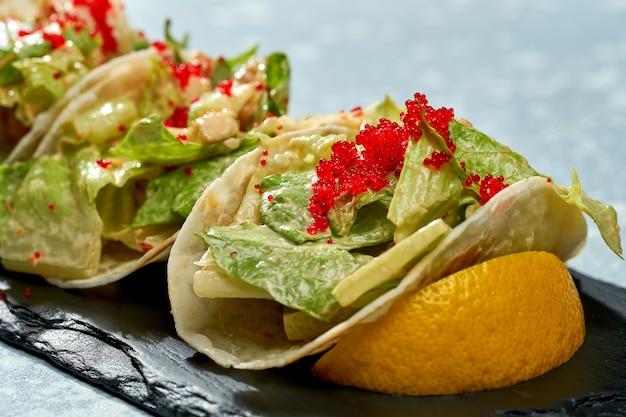 Блюдо мексиканской кухни - тако с лососем, листьями салата, белым соусом и икрой тобико на черной тарелке на синем фоне