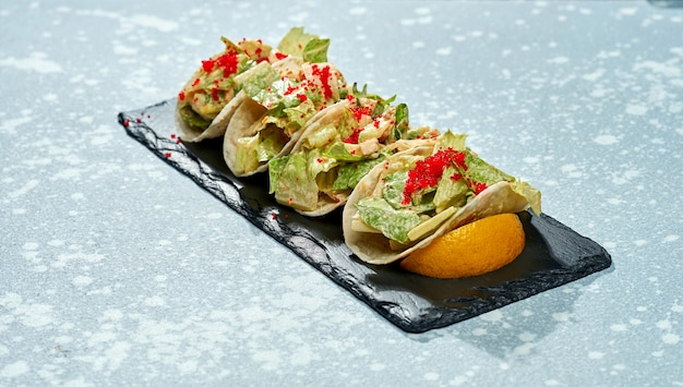 Блюдо мексиканской кухни - тако с лососем, листьями салата, белым соусом и икрой тобико на черной тарелке на синей поверхности
