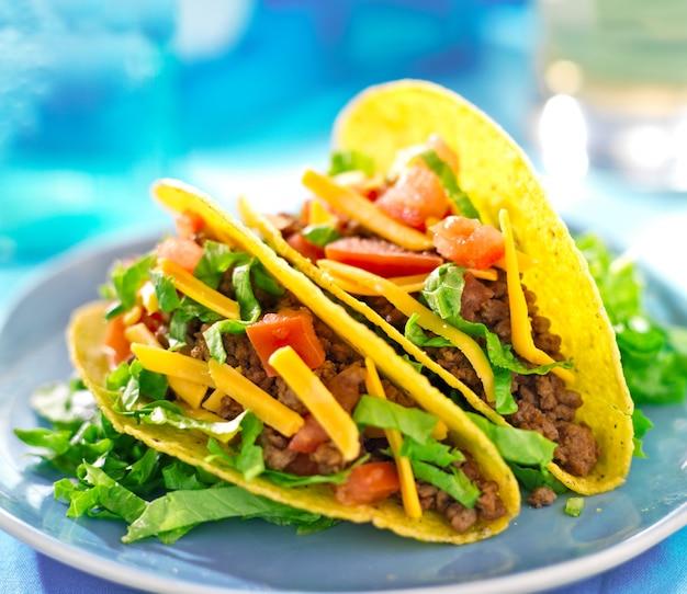 メキシコ料理-牛肉、チーズ、レタス、トマトのハードシェルタコス