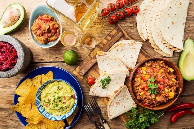Мексиканская пищевая смесь начос, фахитас, тортилья, гуакамоле и соусы сальсы и ингредиенты на деревянной поверхности. вид сверху