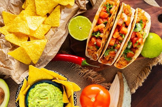 Панорама мексиканской еды. начо, гуакамоле, тако и ингредиенты на деревянных досках. варианты мексиканских чипсов из тако и тортильи с начинкой. плоская планировка. вид сверху