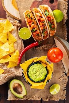 ナチョス、ワカモレ、タコス、食材を使ったメキシコ料理のテーブル。木の板にメキシコのタコスとナチョのトルティーヤチップス。ヒスパニック系メキシコ料理