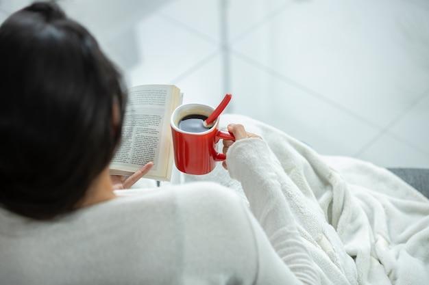 Мексиканская девушка пьет кофе на красной кружке и читает книгу у окна