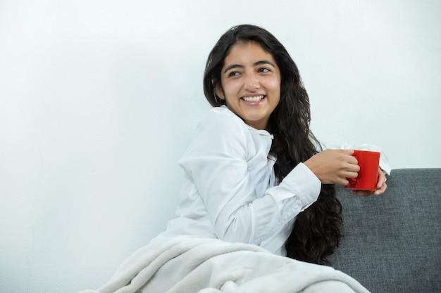 笑って赤いマグカップでコーヒーを飲むメキシコの女の子