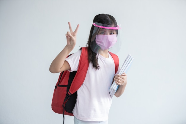 Mexican girl going back to school doing peace sign