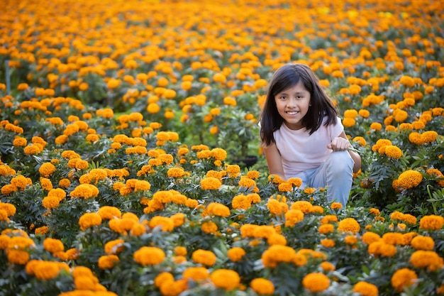 Mexican girl watching and smiling at cempasuchil flowers on the field