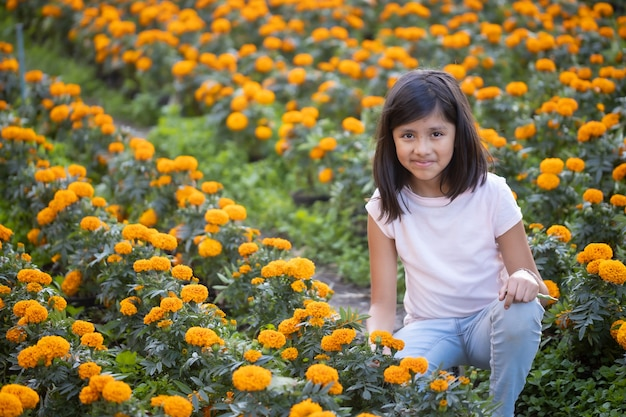 Mexican girl watching and smiling at cempasuchil flowers