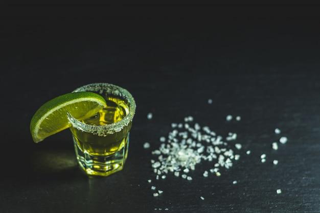 黒い石のテーブルの表面にライムと塩で撮影したメキシコのゴールドテキーラ