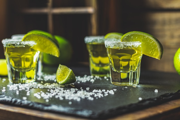 Mexican gold tequila shot with lime and salt on black stone table surface
