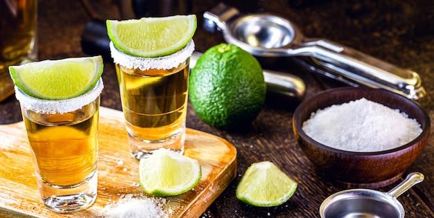 木製のテーブルにレモンと塩とメキシコのゴールドテキーラ