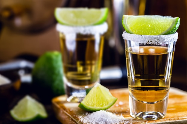 Mexican gold tequila with lemon and salt on wooden surface