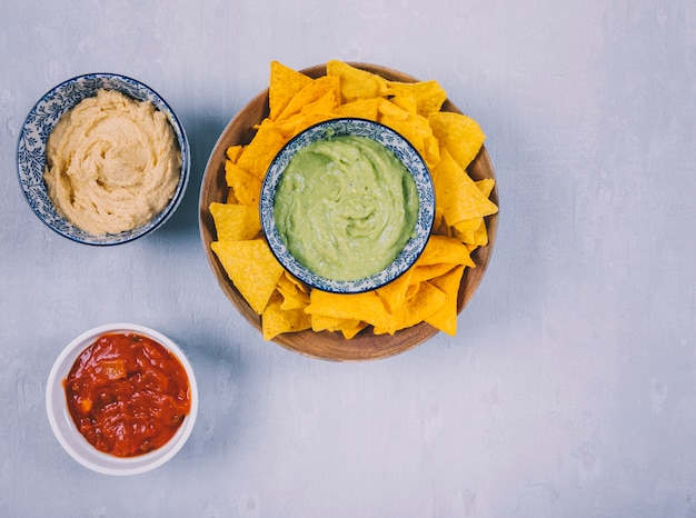 Mexican guacamole dip and nachos tortilla chips with sauce in bowls