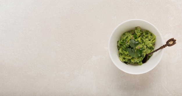 Mexican guacamole sauce in a white bowl on a concrete background, top , copy space