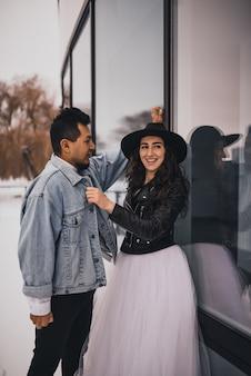 帽子をかぶったメキシコのヒスパニック系の男性と女性は、歩いて笑って抱き合ってキスしています
