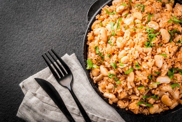 Mexican, latin american cuisine. mexican rice and beans bowl is a recipe made with rice and white beans, homemade, with fresh herbs and herbs. in a frying pan for cooking,  top view copyspace