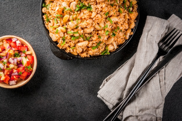 Mexican, latin american cuisine. mexican rice and beans bowl- recipe made with rice and white beans, homemade, with fresh herbs and herbs. in a frying pan for cooking, with salsa, top view copyspace