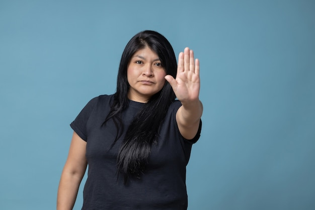 Mexican latin woman doing stop sign with her hand