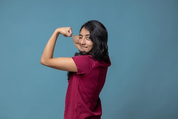 上腕二頭筋と点滅する女の子の力を示すメキシコのラテン女性