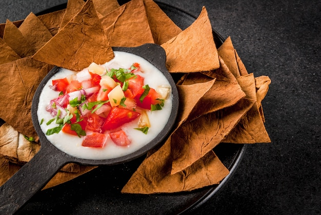 Mexican, latinamerican cuisine. queso blanco recipe - cream cheese, cream, fresh stewed vegetables tomatoes, onions, peppers,  herbs. with baked tortilla chips, black stone table. copyspace