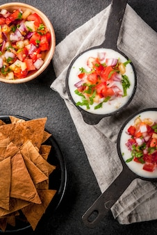 Mexican, latinamerican cuisine. queso blanco recipe - cream cheese, cream, fresh stewed vegetables tomatoes, onions, peppers,  herbs. with baked tortilla chips, black stone table. top view copyspace