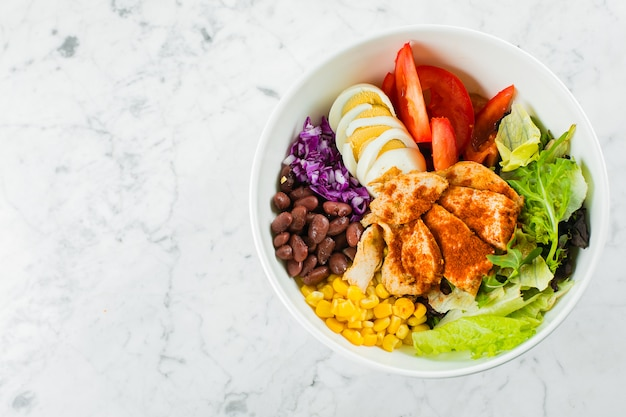 Mexican lunch bowl on marble background. salad bowl with corn, red beans, tomato with red onion, jalapenios, chicken breast. top view, copy space