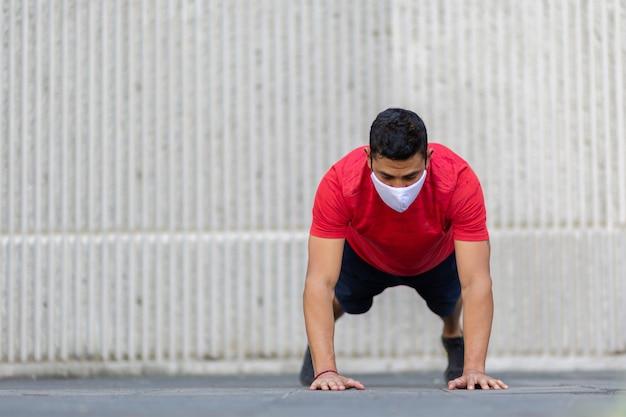 白いフェイスマスクを身に着けている屋外で腕立て伏せをしているメキシコ人男性